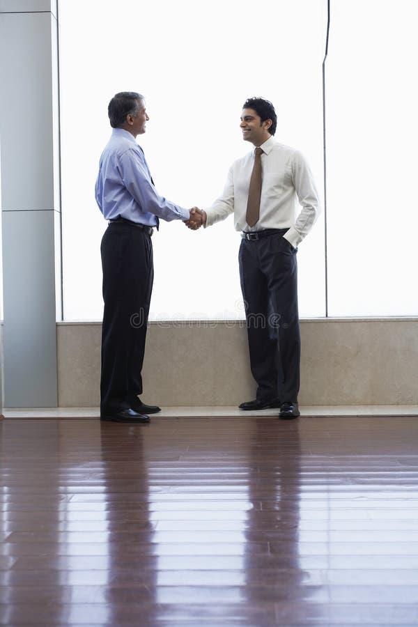 Hommes d'affaires se serrant la main dans le bureau photo stock