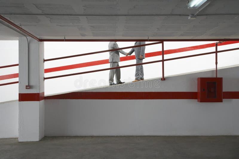 Hommes d'affaires se serrant la main sur la rampe dans le garage image stock