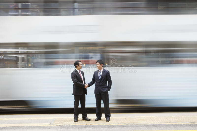 Hommes d'affaires se serrant la main sur la rue passante image stock