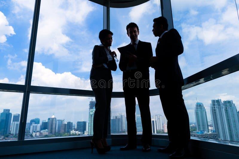Hommes d'affaires se tenant au fonctionnement de windo de bureau photo stock