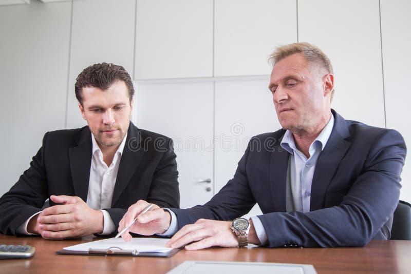 Hommes d'affaires signant le contrat photos stock
