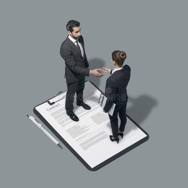 Hommes d'affaires signant un contrat et se serrant la main photographie stock