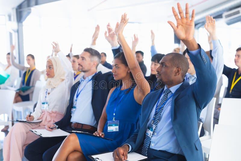 Hommes d'affaires soulevant leurs mains tout en suivant le séminaire d'affaires photos libres de droits