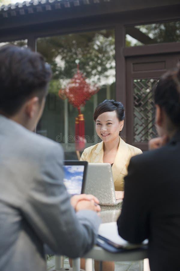Hommes d'affaires souriant et travaillant dehors sur des ordinateurs portables images stock