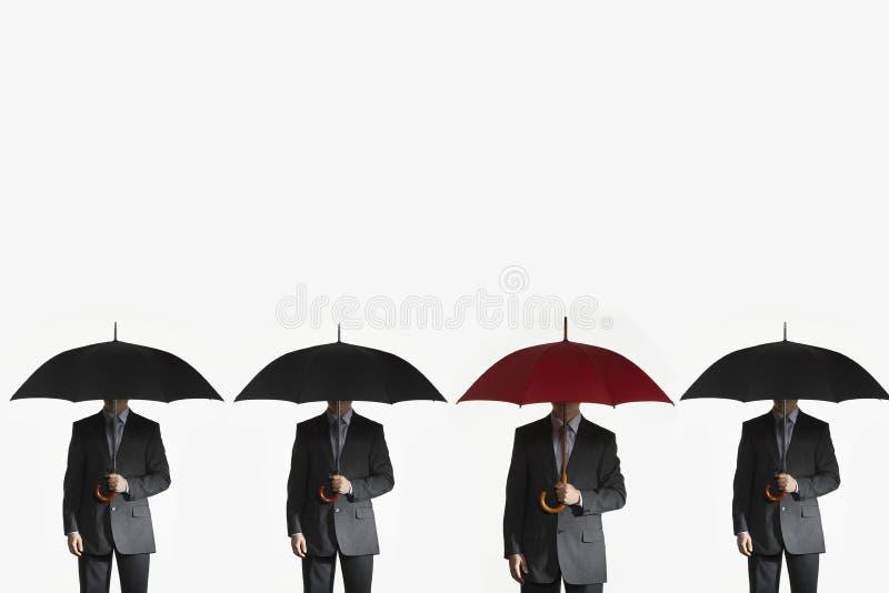 Hommes d'affaires tenant des parapluies dans la rangée photo libre de droits