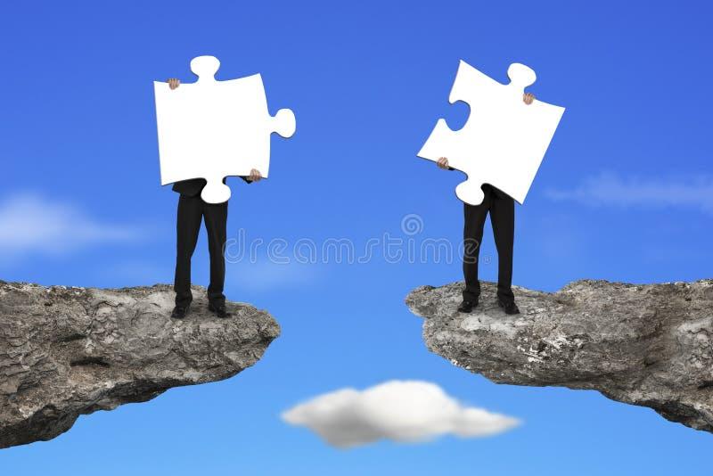 Hommes d'affaires tenant des puzzles denteux pour se relier sur la falaise au ciel photographie stock libre de droits
