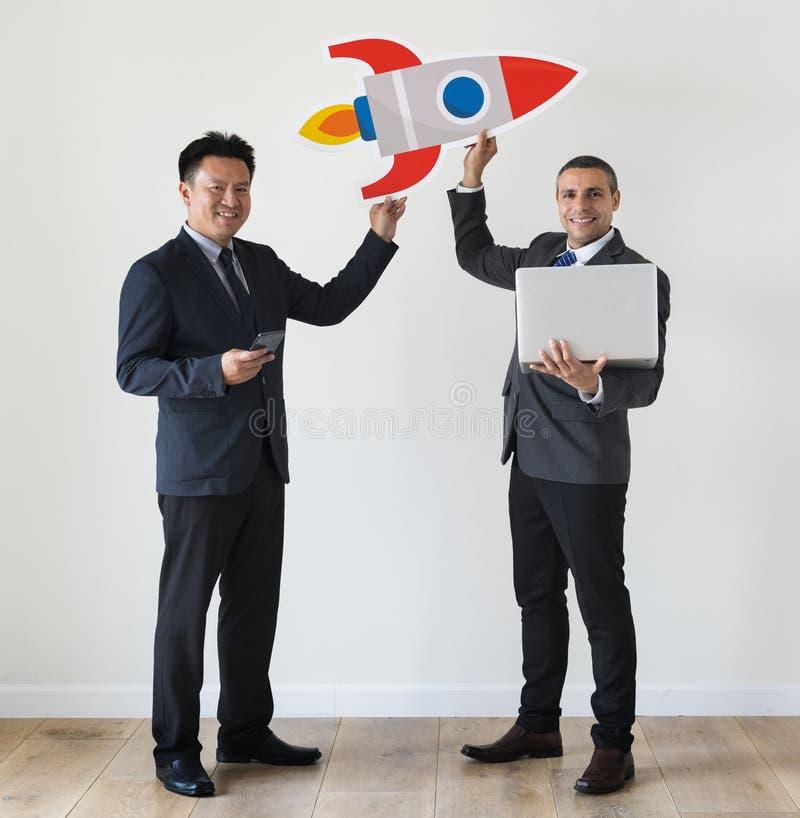 Hommes d'affaires tenant l'icône de fusée au bureau image stock