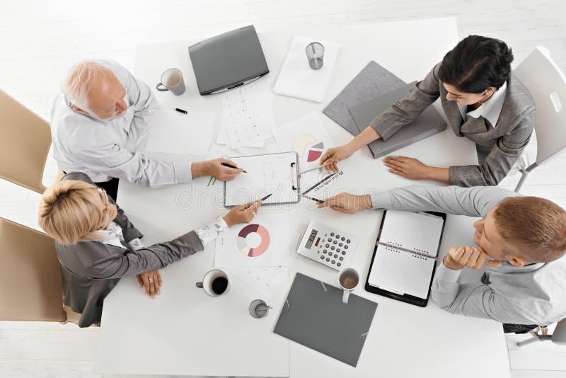 Hommes d'affaires travaillant ensemble lors du contact photographie stock