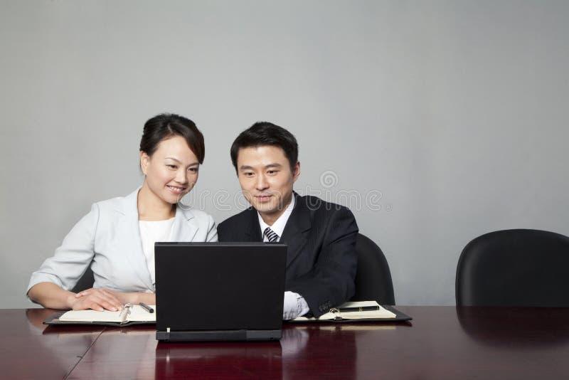 Hommes d'affaires travaillant ensemble sur l'ordinateur portable photo stock