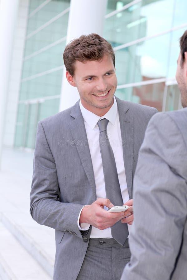 Hommes d'affaires utilisant des smartphones images libres de droits