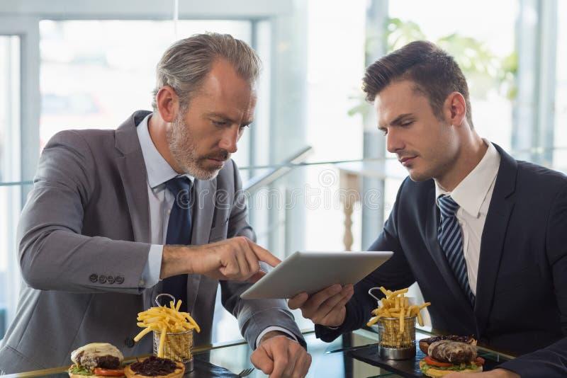Hommes d'affaires utilisant le comprimé numérique dans le restaurant photo libre de droits