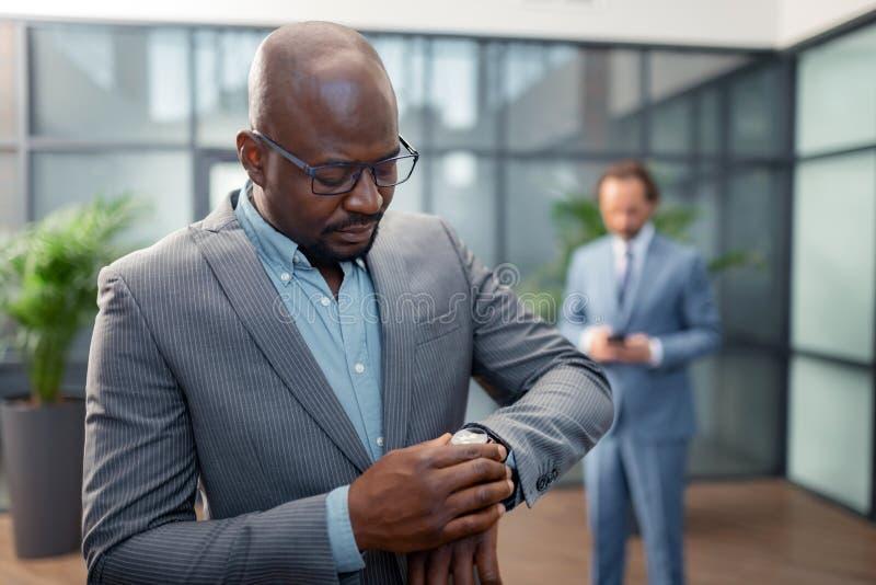 Hommes d'affaires vérifiant l'heure tout en courant tard pour se réunir photos stock