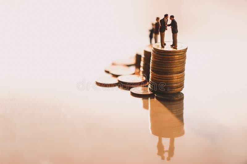 Hommes d'affaires vérifiant la main sur des piles de pièces de monnaie photos libres de droits