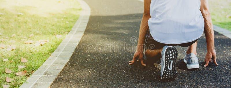 Hommes d'athlète dans la pose de début courant à la manière de marche en parc public Concept sain de la vie et de régime Taille d images stock