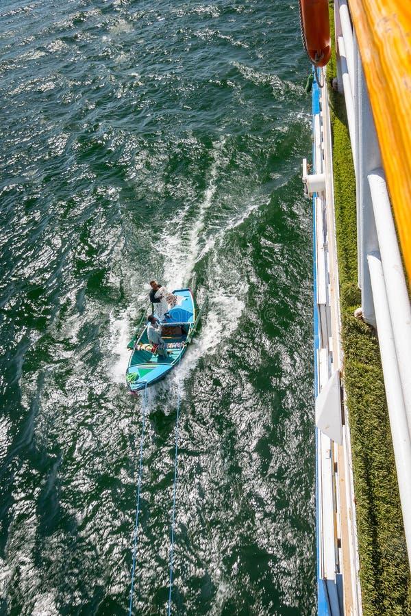 Hommes dans des bateaux qui s'engagent dans les croisières sur le Nil pour se vendre r photo stock
