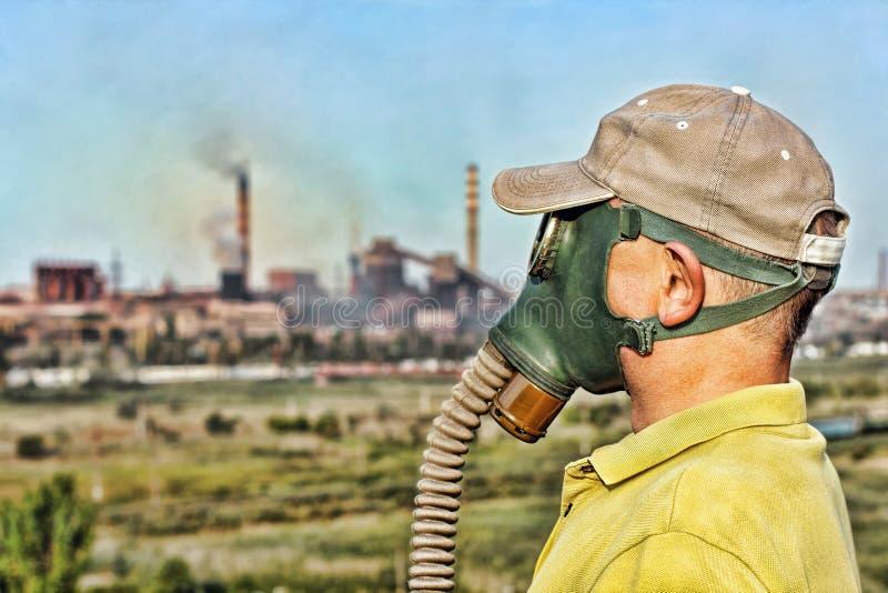Hommes dans le masque de gaz sur le fond industriel de tuyau de tabagisme environme images stock