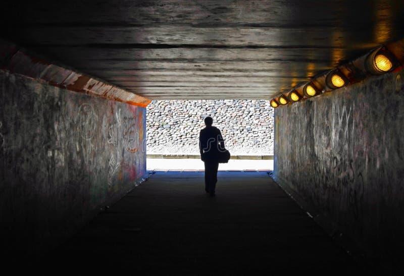 Hommes dans le tunnel foncé photo stock