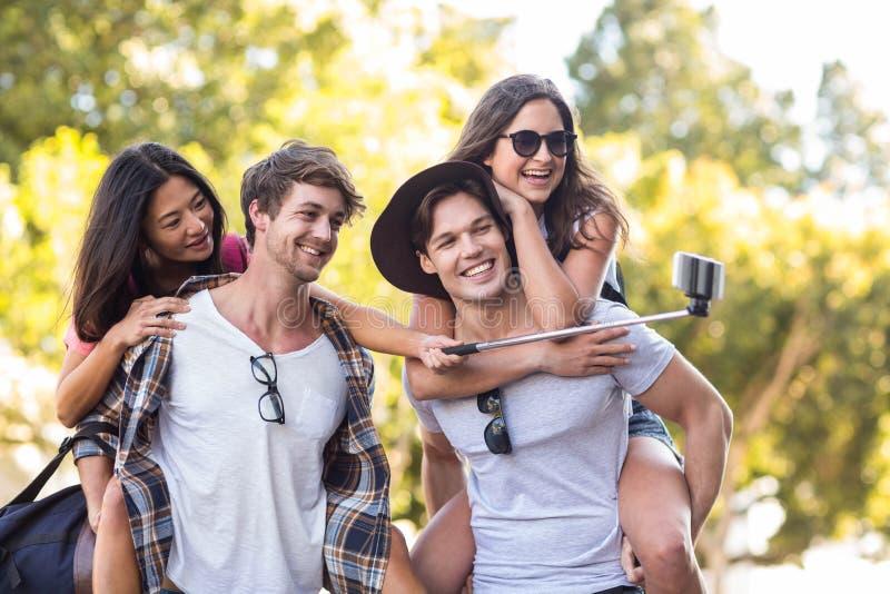 Hommes de hanche donnant sur le dos à leurs amies et prenant le selfie photographie stock libre de droits