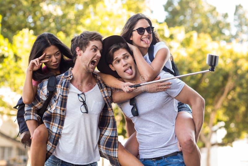 Hommes de hanche donnant sur le dos à leurs amies et prenant le selfie images stock