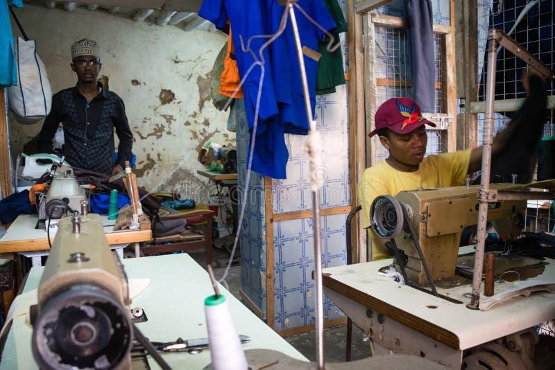 Hommes de tailleur cousant des vêtements, Stonetown photos libres de droits