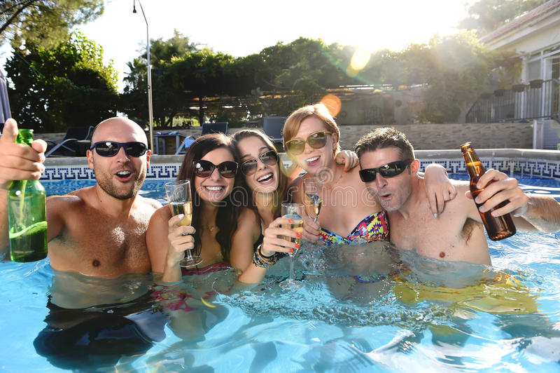 Hommes et femmes attirants heureux dans le bikini ayant le bain à la bière potable de piscine de station de vacances d'hôtel images libres de droits