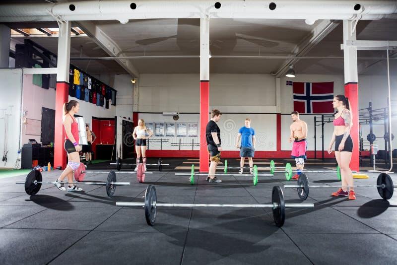 Hommes et femmes avec des Barbells au centre de fitness images libres de droits
