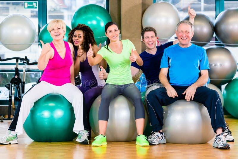 Hommes et femmes s'asseyant sur des boules de forme physique dans le gymnase photographie stock