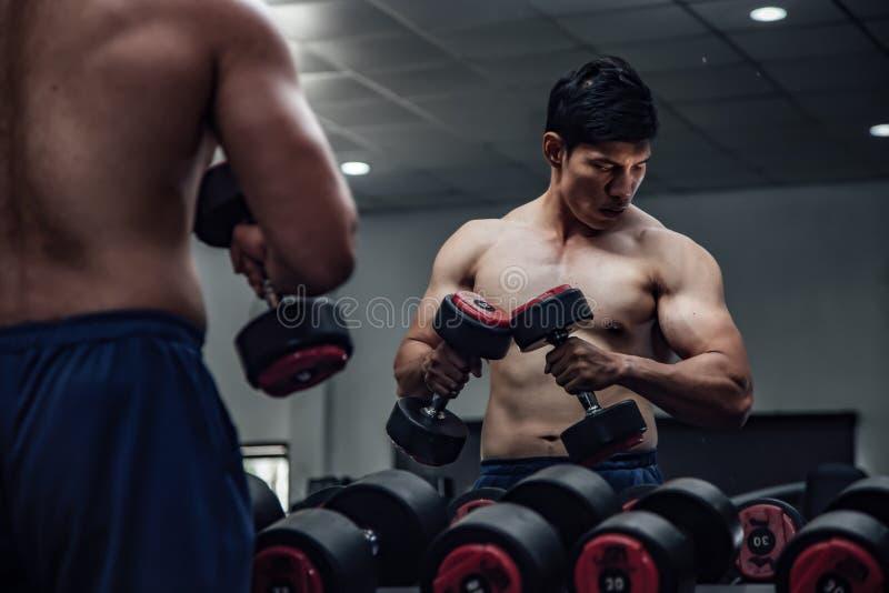 Hommes hauts étroits dans des concepts d'exercice de gymnase pour la santé de corps image libre de droits