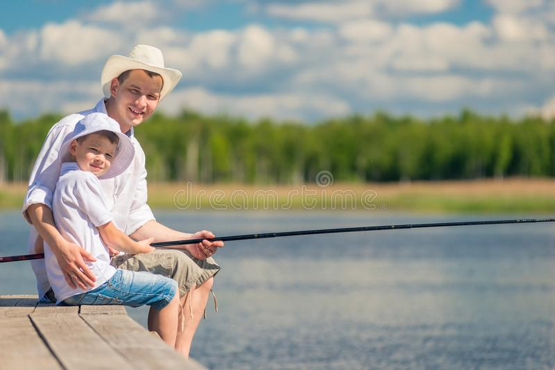 Hommes heureux avec une canne à pêche sur un pilier en bois photographie stock