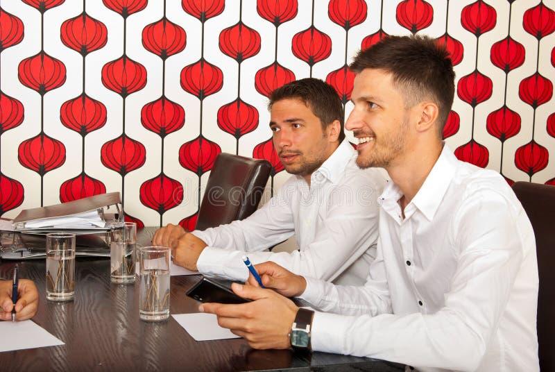 Hommes heureux d'affaires lors de la réunion photo libre de droits