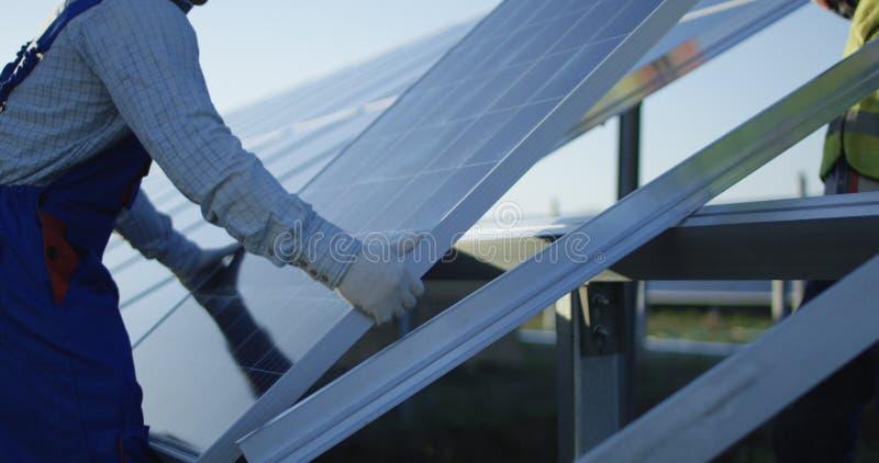 Hommes installant le panneau solaire dehors photographie stock