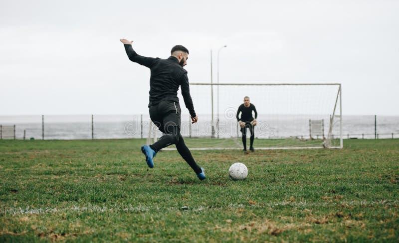 Hommes jouant au football sur le champ près de la mer photographie stock