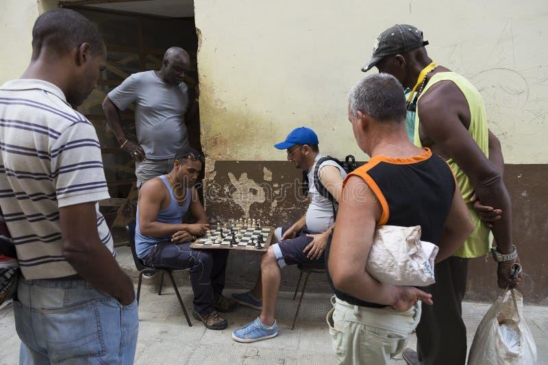 Hommes jouant des échecs sous l'oeil attentif d'autres hommes à vieille La Havane photo libre de droits