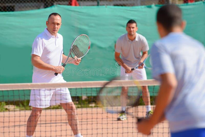Hommes jouant des doubles de tennis image stock