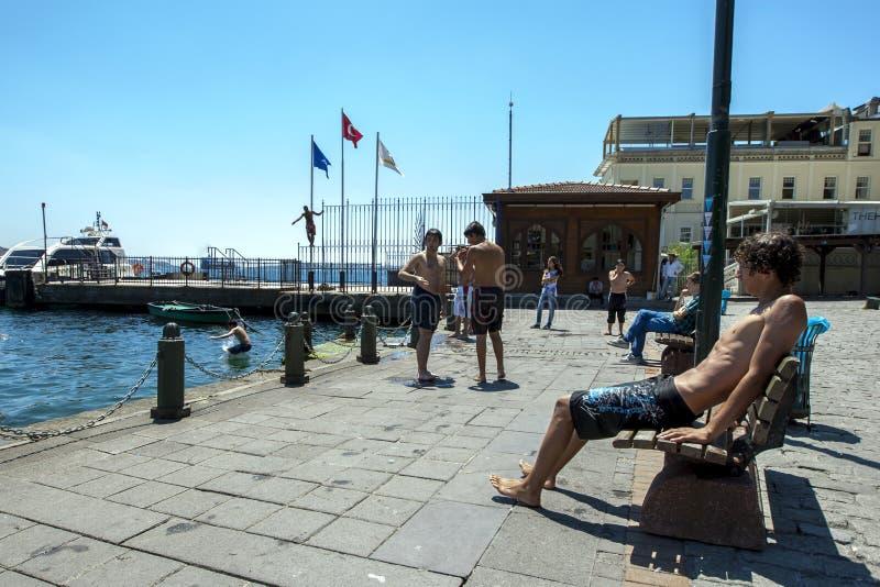 Hommes jouant et nageant dans le Bosphorus chez Ortakoy à Istanbul un jour chaud d'été photographie stock