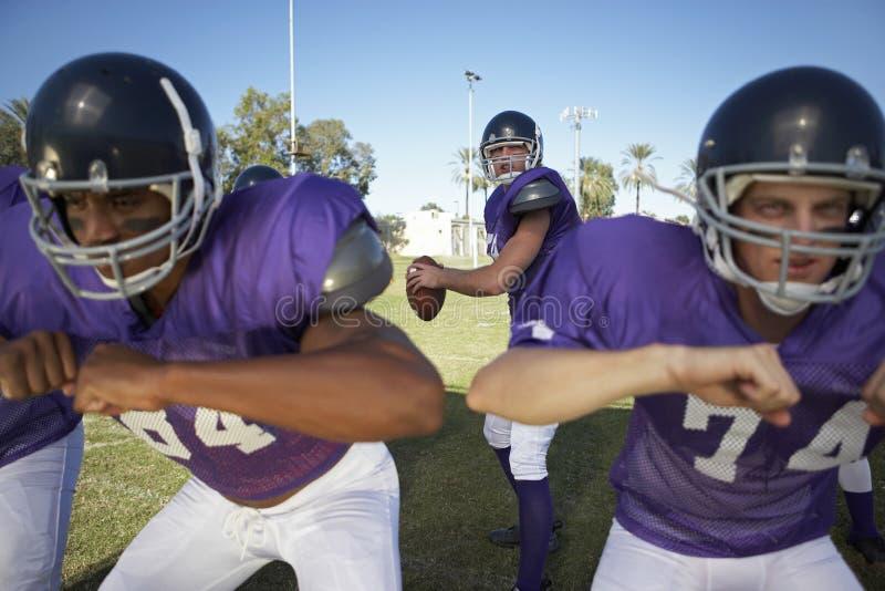 Hommes jouant le football américain sur le champ images libres de droits