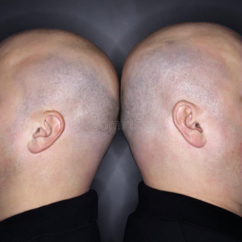 Hommes jumeaux de nouveau au dos. photo stock