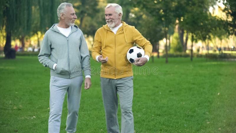 Hommes mûrs dans les vêtements de sport marchant en parc avec la boule, passe-temps de sport, soins de santé photos libres de droits