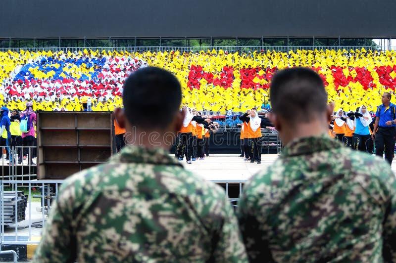 Hommes malaisiens d'armée observant des étudiants pratiquer pour Hari Merdeka en Malaisie, Kuala Lumpur images libres de droits