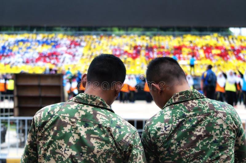 Hommes malaisiens d'armée observant des étudiants pratiquer pour Hari Merdeka en Malaisie, Kuala Lumpur photo libre de droits