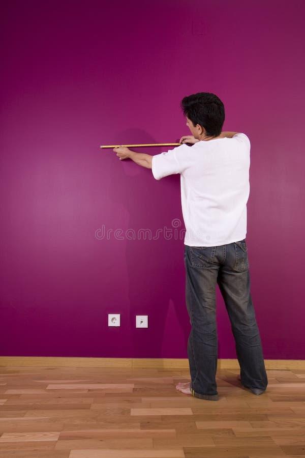 Hommes mesurant le mur photo stock