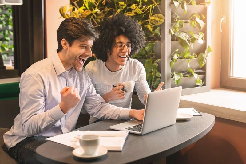Hommes millénaires heureux regardant l'ordinateur portable appréciant de grandes nouvelles images libres de droits
