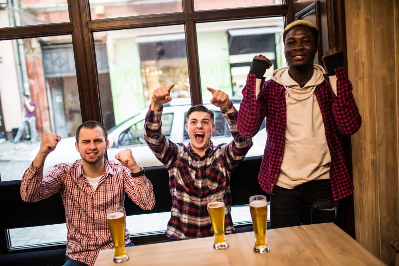 Hommes multiraciaux à la partie de football watcing de bar et à la bière potable image stock