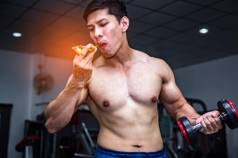 Hommes musculaires forts d'athlète avec les aliments de préparation rapide de pizza Concept malsain de r?gime de consommation photographie stock libre de droits