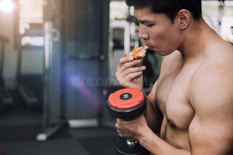 Hommes musculaires forts d'athlète avec les aliments de préparation rapide de pizza Concept malsain de r?gime de consommation photo stock