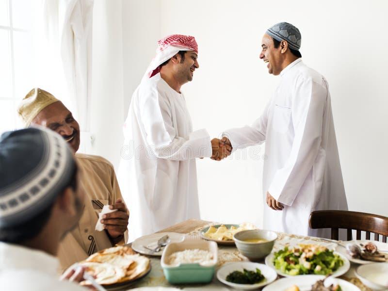 Hommes musulmans se serrant la main à l'heure du déjeuner image stock