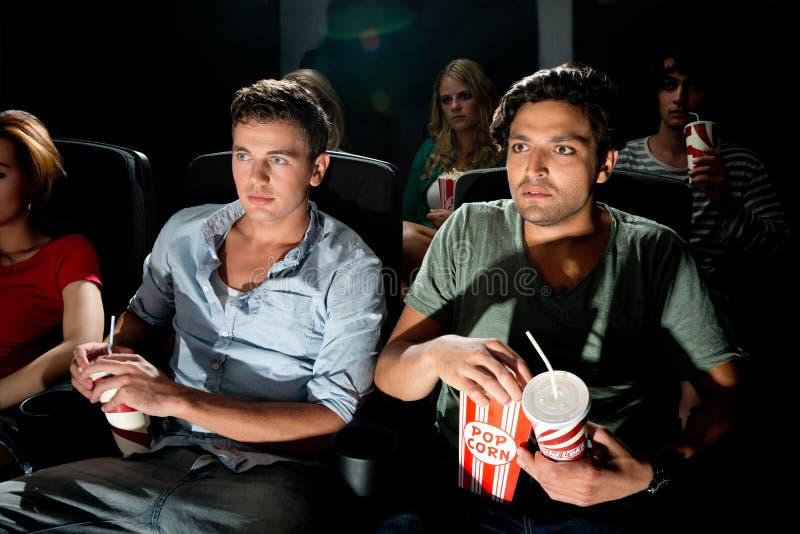 Hommes observant le film dans le cinéma photographie stock libre de droits