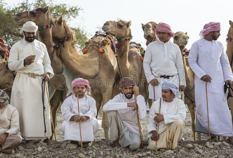 Hommes omanais avec leurs chameaux devant une course photographie stock