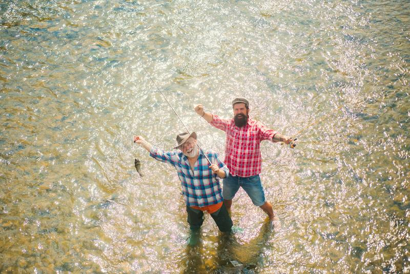 Hommes pêchant en rivière pendant le jour d'été Famille et génération - concept de vacances d'été et de personnes Homme pêchant e images stock