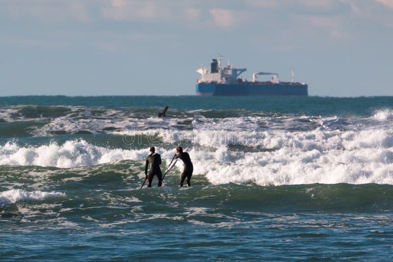 Hommes paddleboarding à bord dans les vagues, bateau d'approvisionnement dans le backgro photos stock